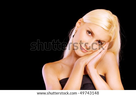Beautiful blonde with palms at face, isolated on black background. - stock photo