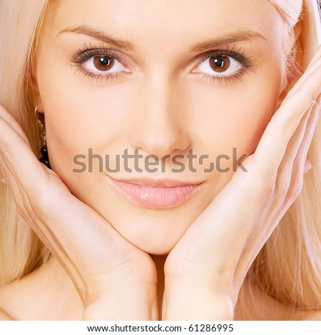 Beautiful blonde with palms at face, square.