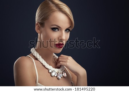Beautiful blonde with red lipstick and the necklace around the neck posing in the studio - stock photo