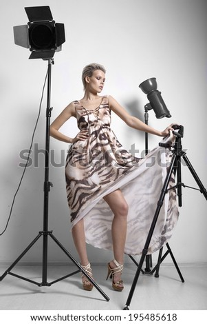 Beautiful blonde with short hair in a dress. posing in studio near light sources on a tripod
