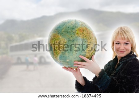 Beautiful blonde with valise and globe on background