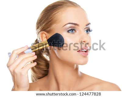 Beautiful blonde woman applying blusher or foundation powder to her cheek with a large soft cosmetics brush, beauty portrait isolated on white
