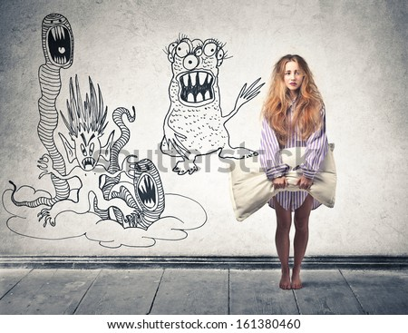 beautiful blonde woman awakened by nightmares with a pillow in hand - stock photo