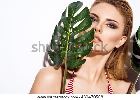 Beautiful blonde woman between palm leaves. Beauty summer make up photo. - stock photo
