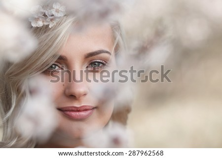 beautiful blonde woman closeup face portrait in a flowered spring garden - stock photo