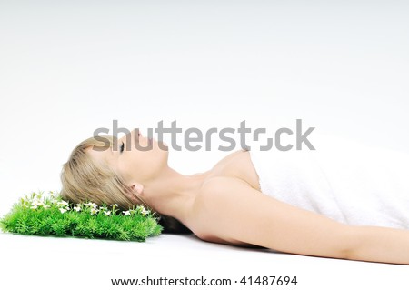 beautiful blonde woman face isolated on white with small green peace of grass - stock photo