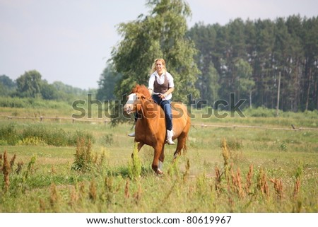 Beautiful blonde woman galloping on chestnut horse without saddle and bridle