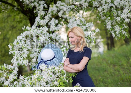 Beautiful blonde woman head and shoulders portrait in a flowered spring garden, wearing big white and blue hat.Youth and beauty.Flowers of Spring. .Natural background with flowering cherries.  - stock photo