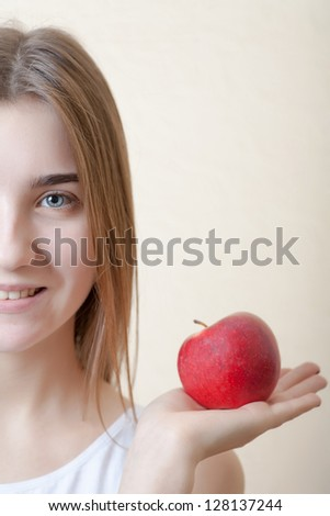 Beautiful blonde woman holding a red apple in left hand - health concept. Pretty smile deep blue eyes half of the face