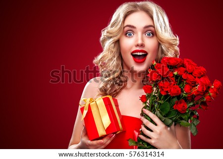 Beautiful blonde woman holding bouquet of red roses and gift. Saint Valentine and International Women's Day, Eight March celebration.