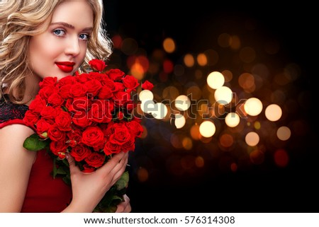 Beautiful blonde woman holding bouquet of red roses on bokeh background. Saint Valentine and International Women's Day, Eight March celebration.