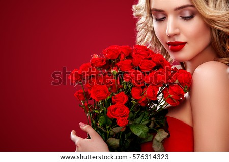 Beautiful blonde woman holding bouquet of red roses. Saint Valentine and International Women's Day, Eight March celebration.
