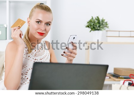 Beautiful blonde woman holding golden credit card and cellphone looking in camera. Young lady buying dresses and new stuff in house via internet. Shopping, consumerism, delivery and present concept - stock photo
