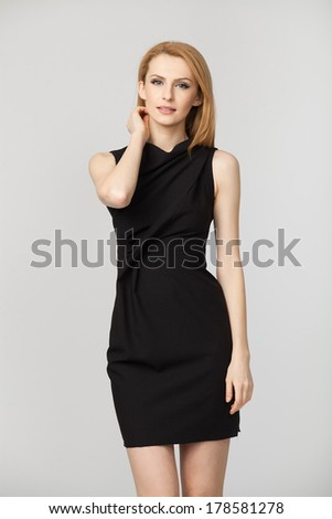 Beautiful blonde woman in back dress on grey background - stock photo
