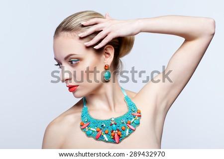 Beautiful blonde woman in bijouterie  on grey background - stock photo