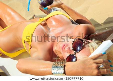 Beautiful blonde woman in bikini on the beach - stock photo