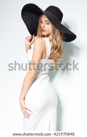 Beautiful blonde woman in black hat and white elegant evening dress posing on isolated background.Fashion look.Stylish clothing.Studio shot - stock photo