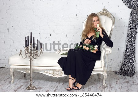 Beautiful blonde woman in dress in luxury interior. - stock photo