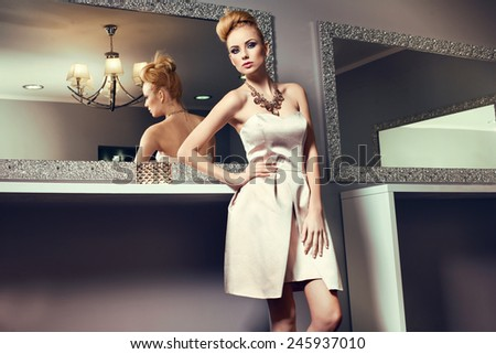 beautiful blonde woman in elegant dress, big necklace in nice interior  - stock photo