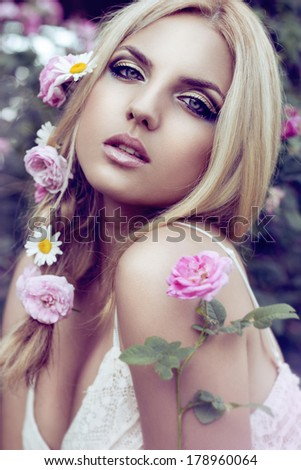 Beautiful blonde woman in garden with pink roses. Beauty portrait, outdoor - stock photo