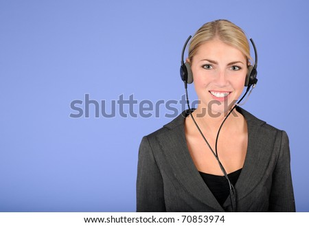 Beautiful blonde woman in gray business suit smiling as she talks on the phone through headset - stock photo