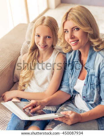 Beautiful blonde woman in jeans shirt and her teenage daughter are holding a photo album, looking at camera and smiling while sitting on couch at home - stock photo