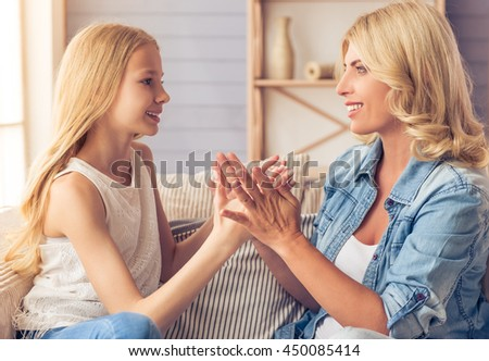Beautiful blonde woman in jeans shirt and her teenage daughter are playing with hands, looking at each other and smiling while sitting on couch at home