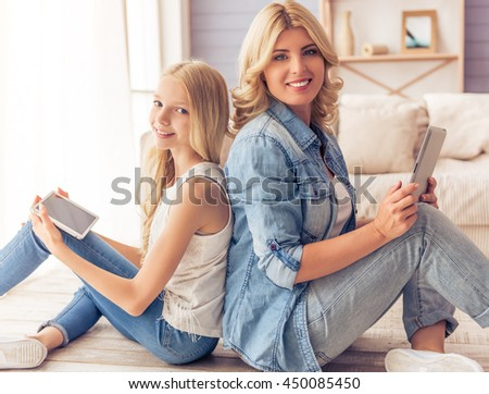 Beautiful blonde woman in jeans shirt and her teenage daughter are using tablets, looking at camera and smiling while sitting back to back on the floor at home - stock photo