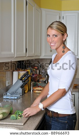 Beautiful blonde woman in kitchen breaking broccoli to put into salad