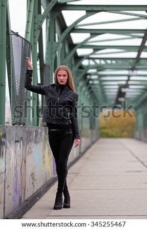 Beautiful blonde woman in leather jacket and leggings on a bridge