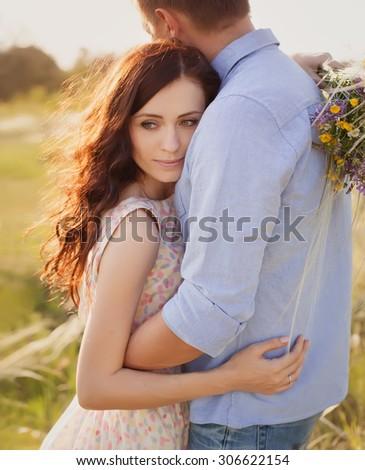 beautiful blonde woman in love hugging her boyfriend - stock photo