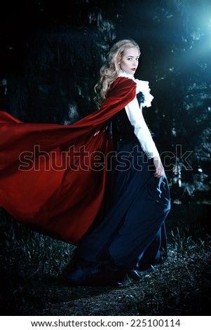 Beautiful blonde woman in  old-fashioned dress and red cloak in a fairy forest. - stock photo