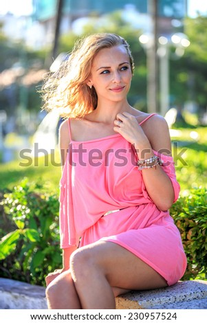 Beautiful Blonde Woman In Pink Dress Sitting In The Park - stock photo