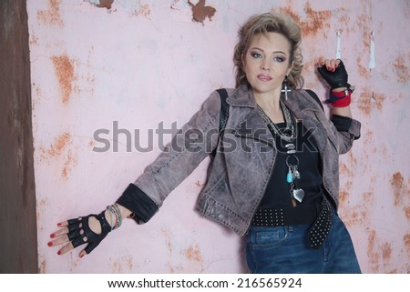 Beautiful blonde woman in rock style posing near the old wall - stock photo