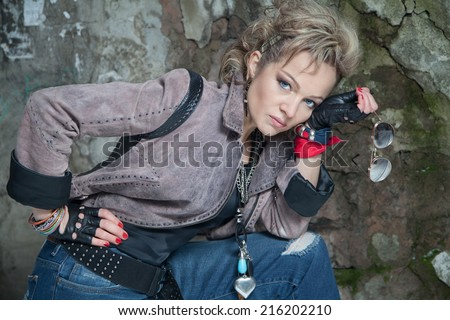 Beautiful blonde woman in rock style posing on street and looking at the camera - stock photo