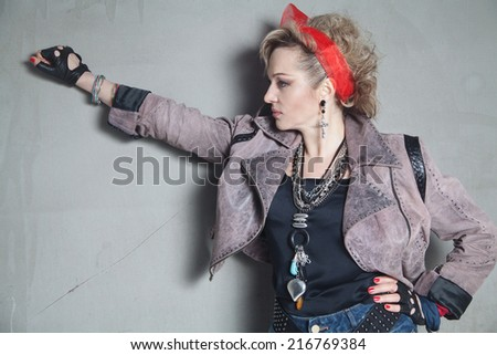 Beautiful blonde woman in rock style stands in profile near concrete wall with a raised hand - stock photo