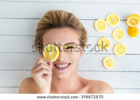 beautiful blonde woman laying on a white wooden background next to slices of lemon, having a slice of lemon on the eyes and smiling  - stock photo