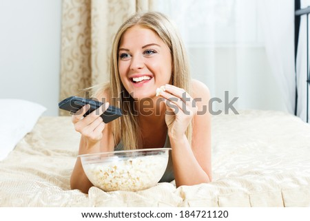 Beautiful blonde woman lying on her bed,eating popcorn and watching tv,Leisure time - stock photo