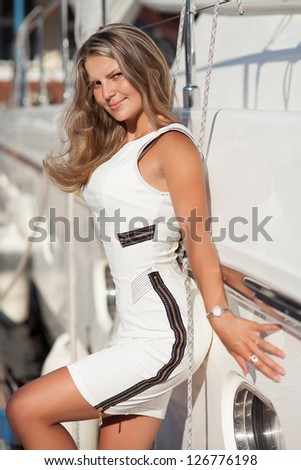 Beautiful blonde woman near yacht enjoy moment of happiness at vacation on sea. Playful alluring sexy girl posing at summer day in bay. gorgeous lady in white dress having fun. Fashion model at yacht