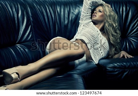 Beautiful blonde woman on black couch - stock photo