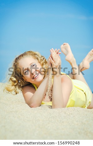 beautiful blonde woman on sand beach. Slim happy girl resting smiling and enjoying summer sun. Romantic lady having fun at vacation holidays. Alluring model at exotic spa resort