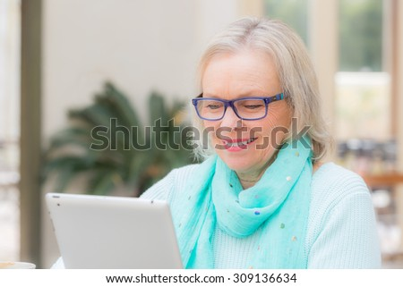Beautiful blonde woman operates tablet computer at outdoor cafe