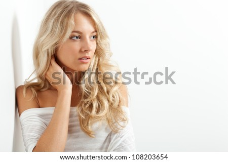 beautiful blonde woman portrait near white wall, copy space - stock photo