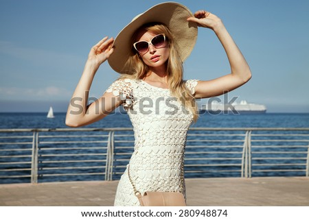 Beautiful blonde woman posing at sunny summer day. Girl wearing fashionable sunglasses and hat. - stock photo