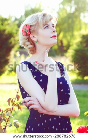 Beautiful blonde woman posing in the rose garden in a retro dress and looking dreamy and thoughtful - stock photo
