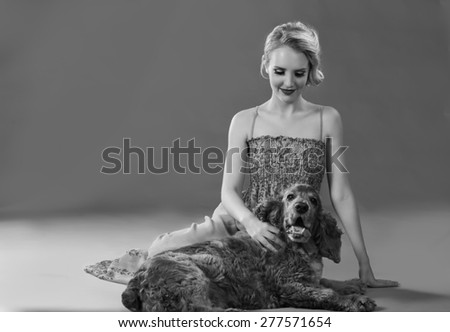 Beautiful blonde woman seating on ground with adorable dog in black and white - stock photo