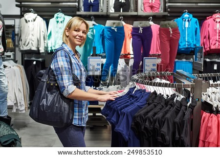 Beautiful blonde woman shopping in clothing store - stock photo
