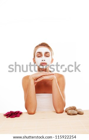 Beautiful blonde woman sitting at a table with her eyes closed meditating in a face mask isolated on white