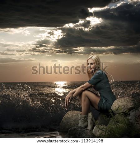 Beautiful Blonde Woman Sitting near the Sea - stock photo