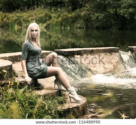 Beautiful Blonde Woman Sitting near the Waterfall - stock photo